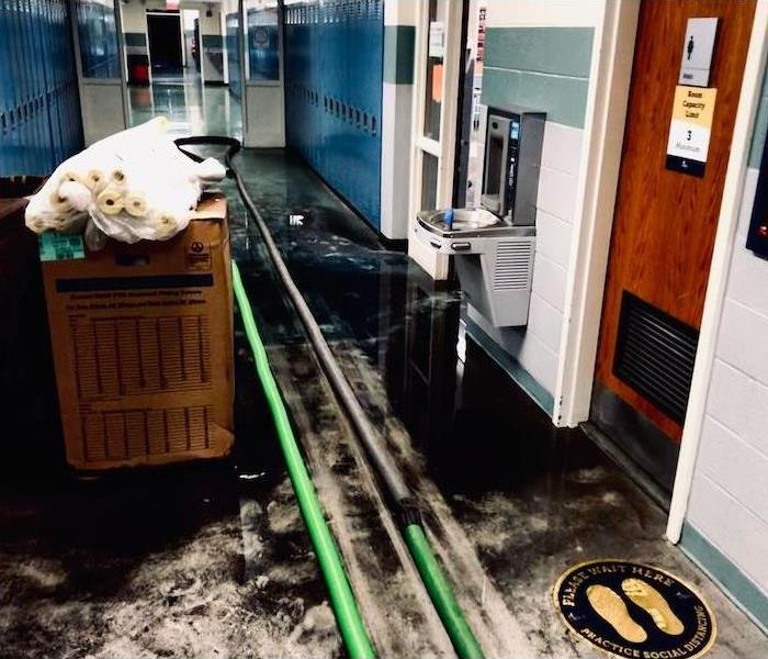 School floor with black oil and SERVPRO cleanup equipment
