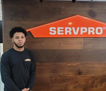 Pedro posing in a black SERVPRO shirt by our sign