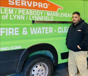 male employee standing in front of a SERVPRO van